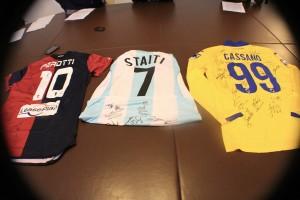 Le magliette di Genoa, Sampdoria ed Entella firmate dalle squadre che andranno all'asta.